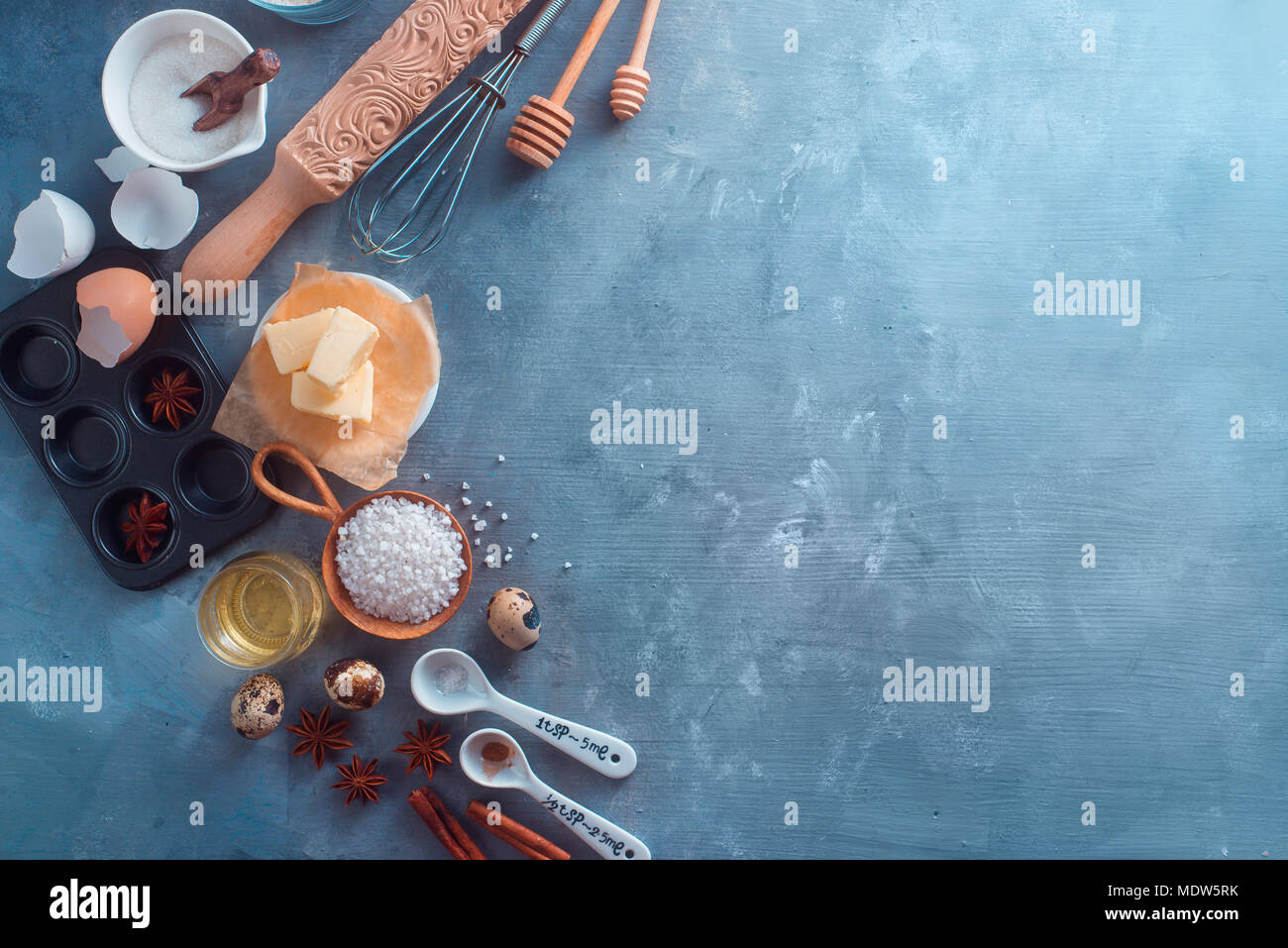 Cooking concept with baking tools and ingredients. Rolling pin, honey spoons, muffin tin, whisk, flour, butter on a concrete background, header with copy space - Stock Image