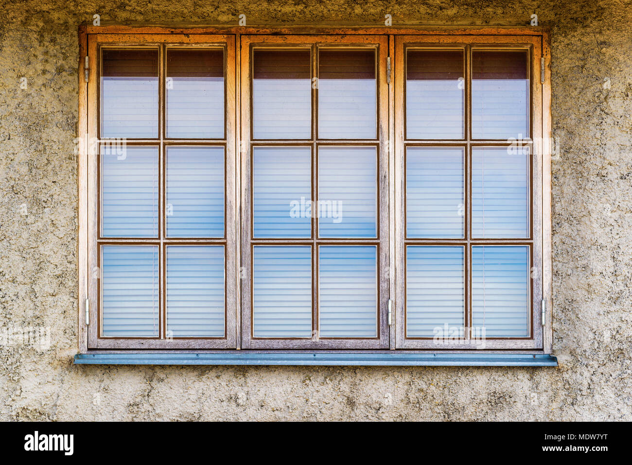 Three windows with blinds on a gray facade