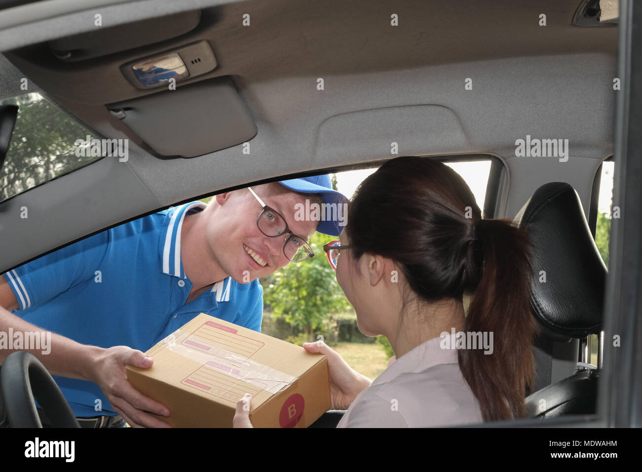 woman receive package from delivery man. male postal courier person deliver cardboard box to female adult on car - Stock Image