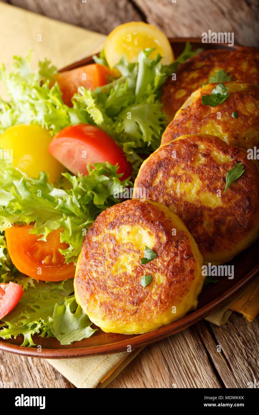 Ecuadorian potato pancakes llapingachos and fresh salad close-up on a plate on a table. vertical - Stock Image