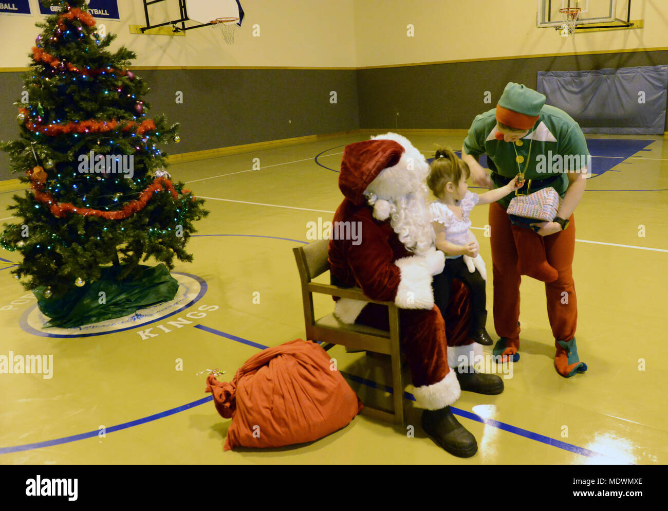 Santa Claus and his head elf give Christmas gifts to a young girl at ...