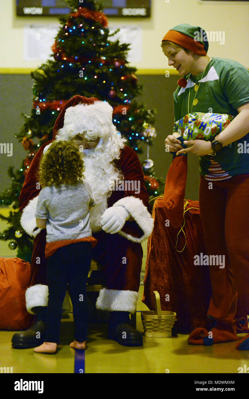 A Port Lions girl receives a gift from Santa Claus, while his elf ...