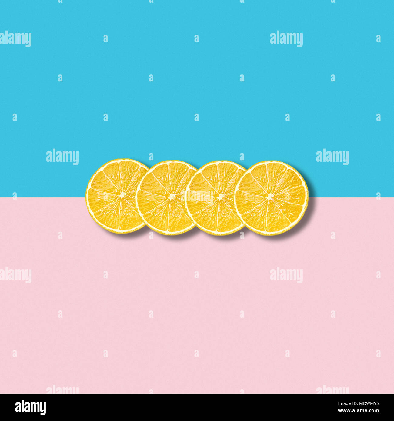 Minimal abstract illustration with group of lemon slices on pastel pink and turquoise background - Stock Image