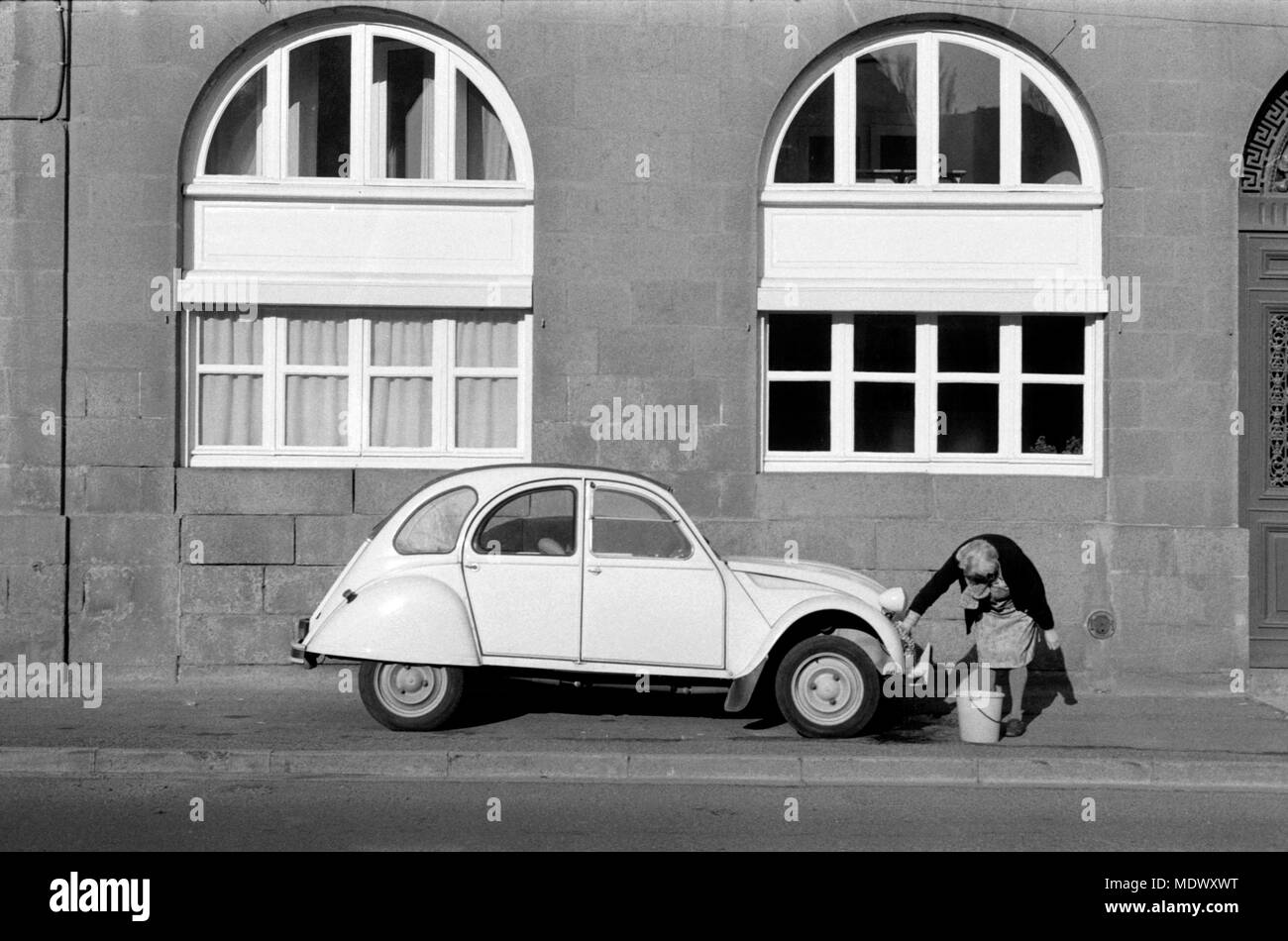 AJAXNETPHOTO. ST.BRIEUC, FRANCE. - CLEAN UP - CLEANING A CITROEN DEUX CHEVAUX 2CV ON THE SIDEWALK.  PHOTO:JONATHAN EASTLAND/AJAX REF:9112_36001 - Stock Image