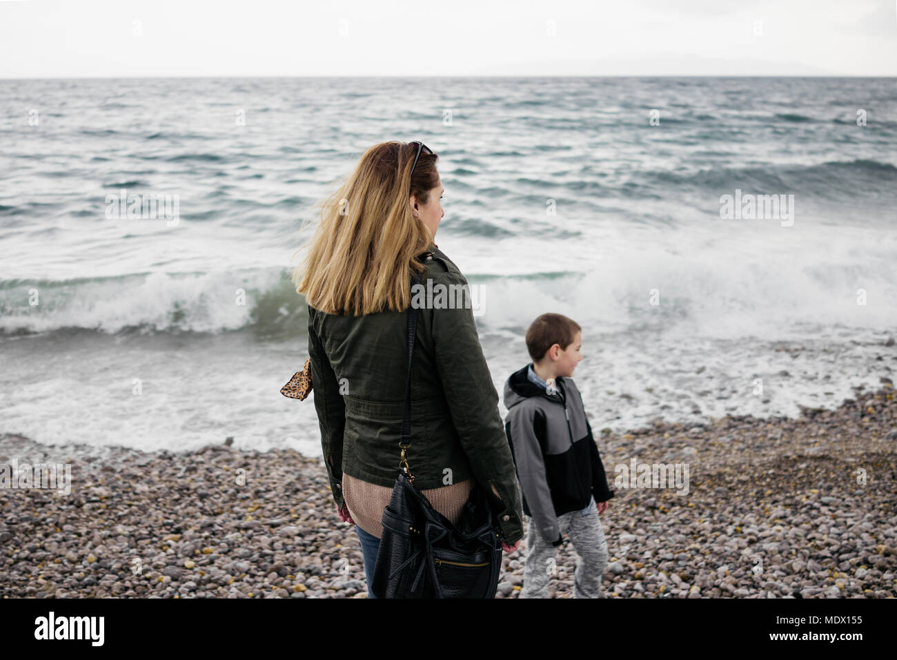 Mother and her son strolling by the sea - Stock Image