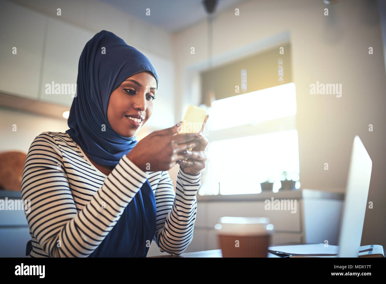 Smiling young Arabic woman wearing a hijab sitting in her kitchen at home sending a text message and using a laptop Stock Photo