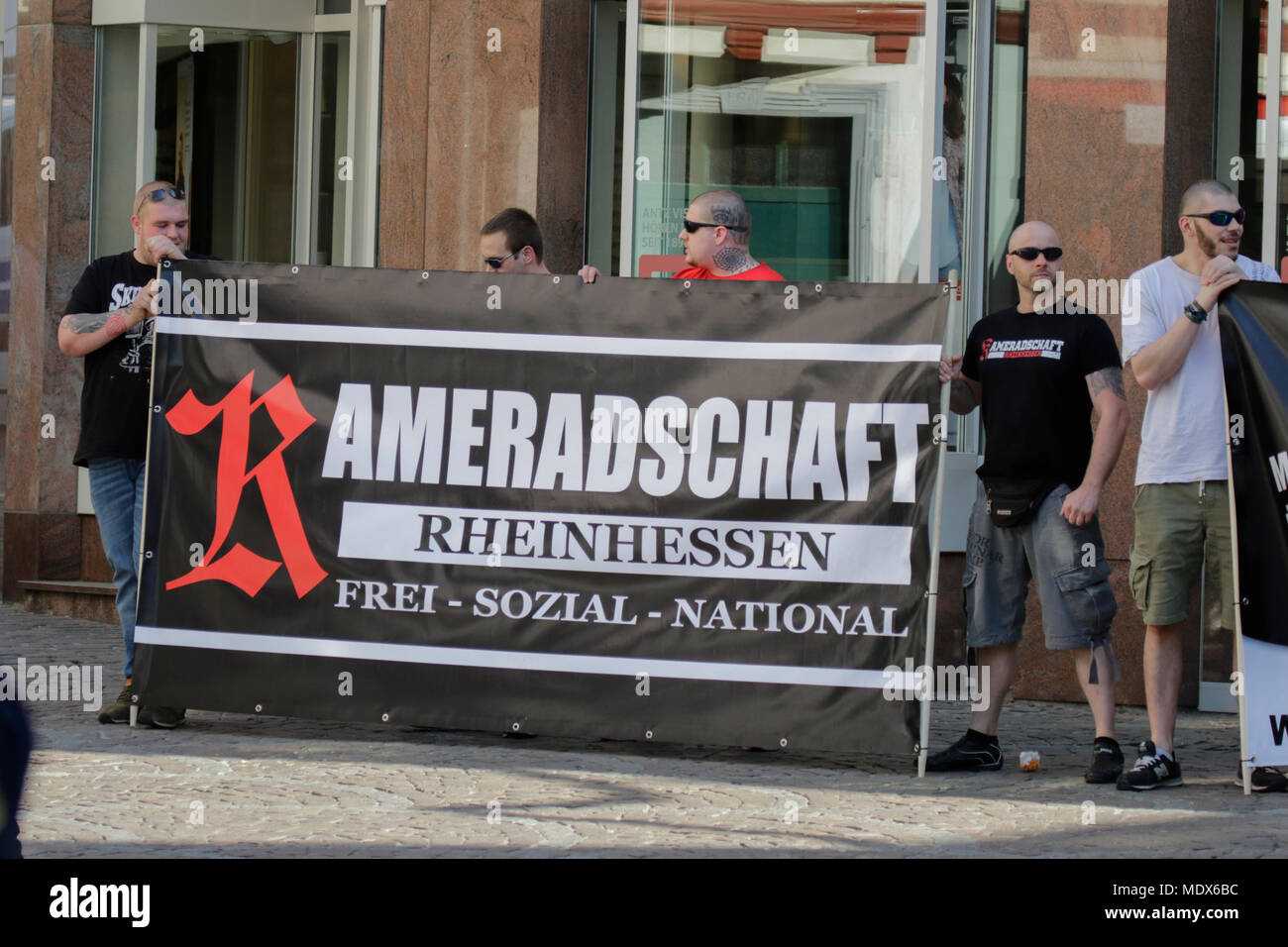 Alzey, Germany. 20th April 2018. Members of the Kameradschaft Rheinhessen (comradeship Rhine-Hesse) hold a banner of their group. A handful of activists from the far right minor party Die Rechte (The Right) and members of right-wing comradeships hold a vigil in the Rhenish Hessian city of Alzey under the slogan 'Multiculturalism kills! Stop foreign infiltration!' against immigration and foreigners. The protest took part on the birthday of Adolf Hitler. The protested was confronted by a counter-protest from different left and democratic groups and parties. Both groups were separated by riot pol - Stock Image