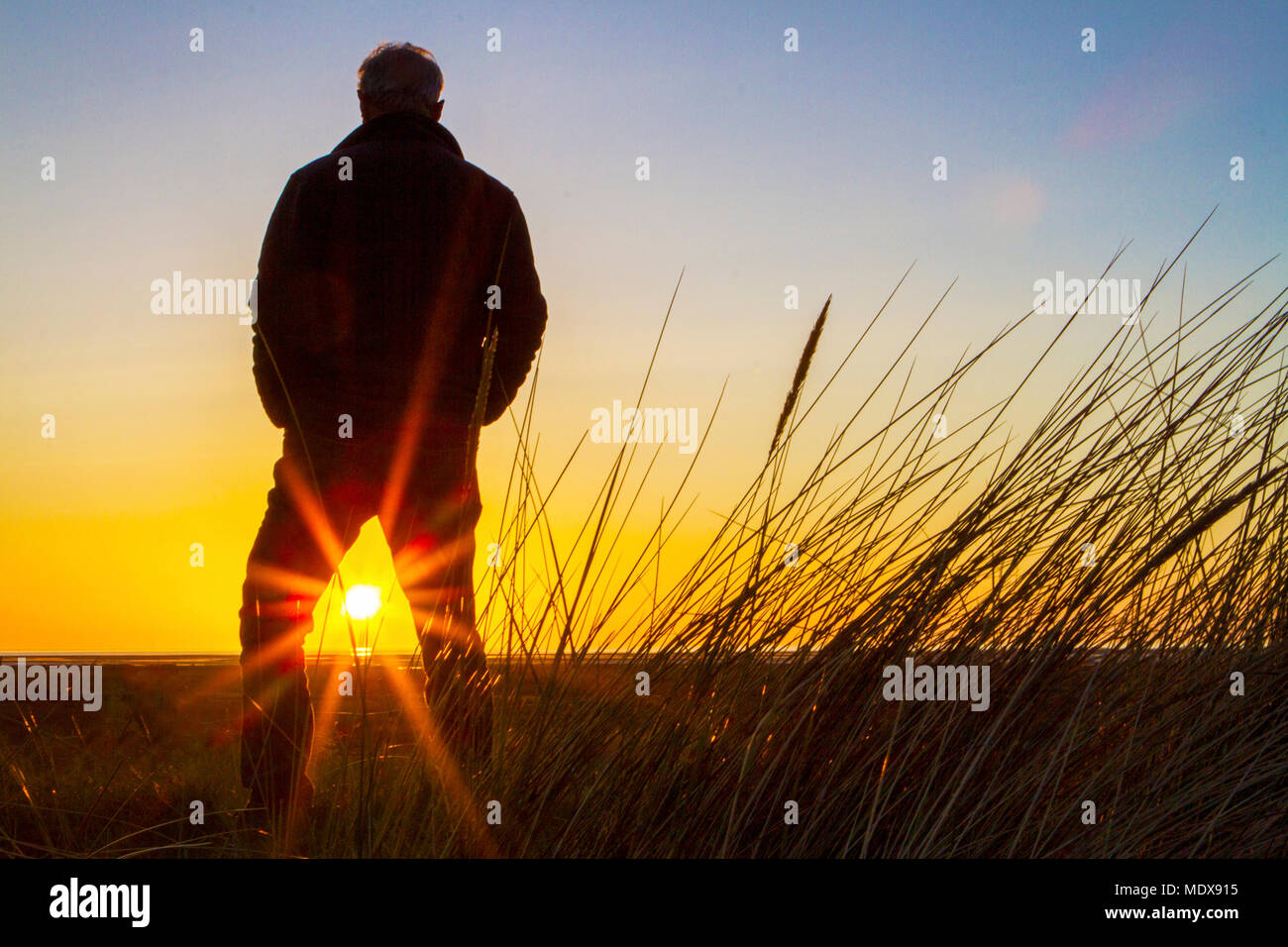 Stunning Sunset, Southport, Merseyside. 20th April 2018. UK Weather. A man stands on the sand dunes watching as the sunset drops into the horizon over Southport beach in Merseyside.  Credit: Cernan Elias/Alamy Live News Stock Photo