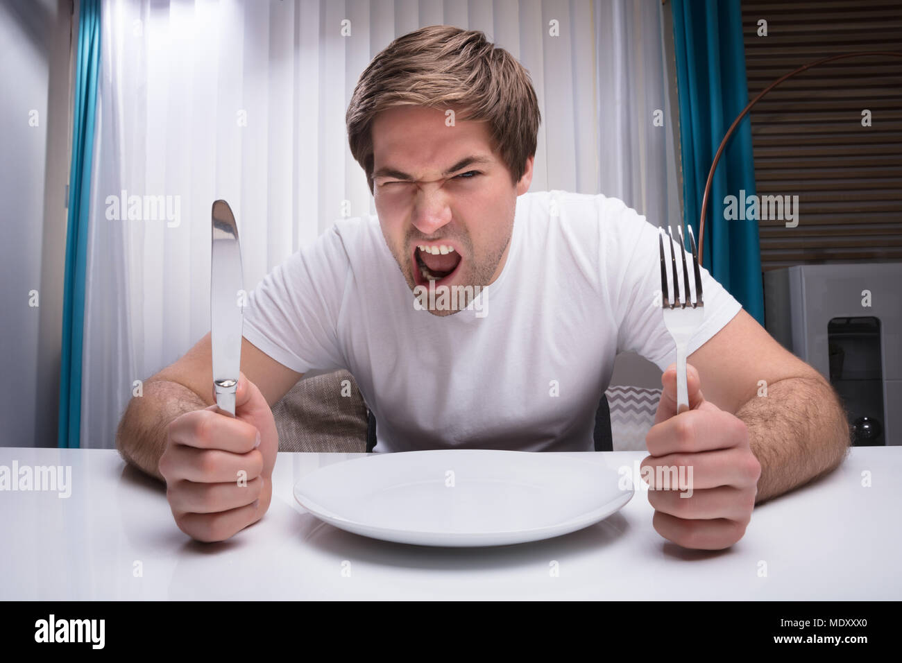 Angry Man Holding Knife And Fork With Empty Plate On Table Stock Photo -  Alamy