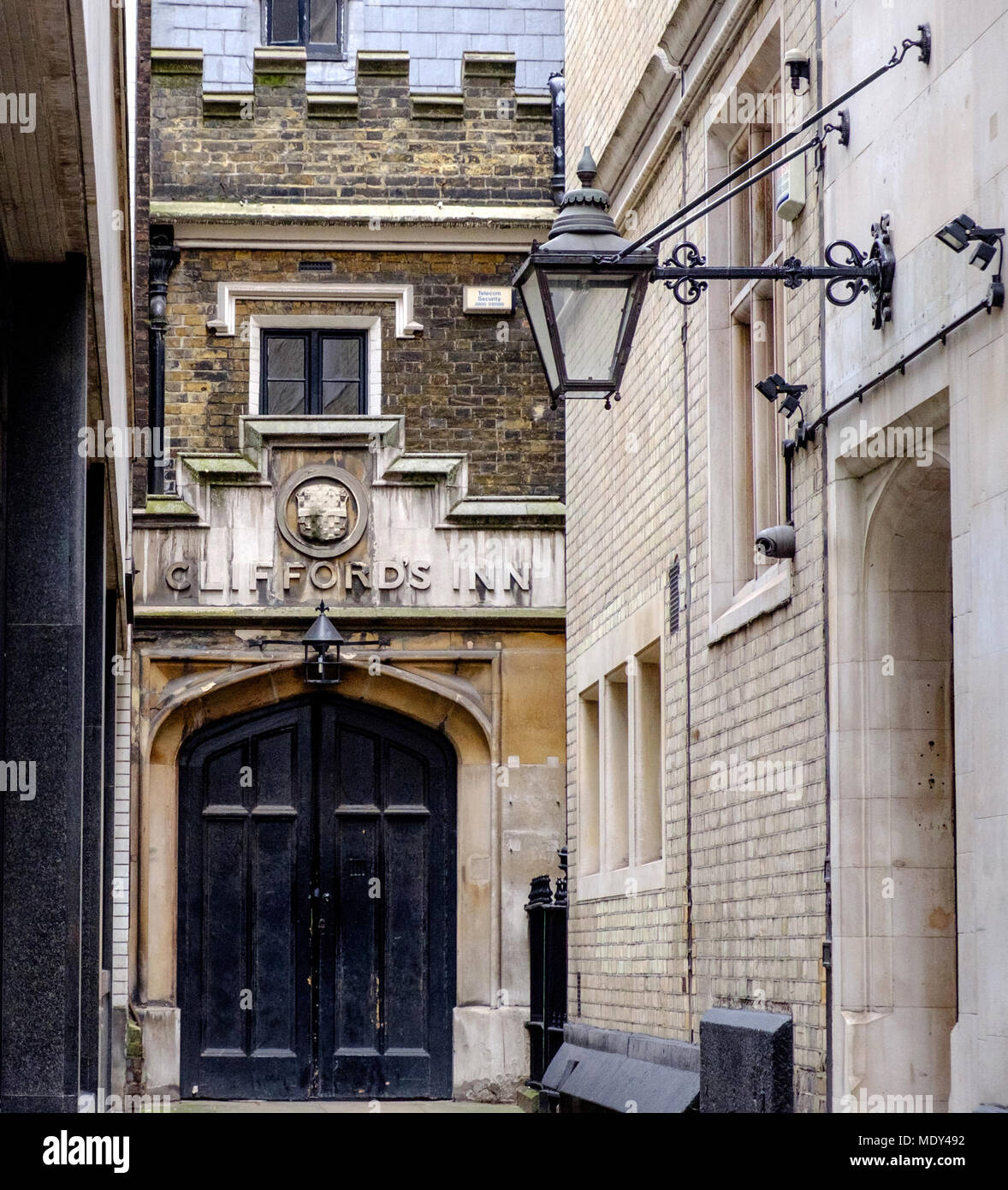Old wrought iron street light extended from building in front of Clifford's Inn, in the City of London next to Chancery Lane. - Stock Image