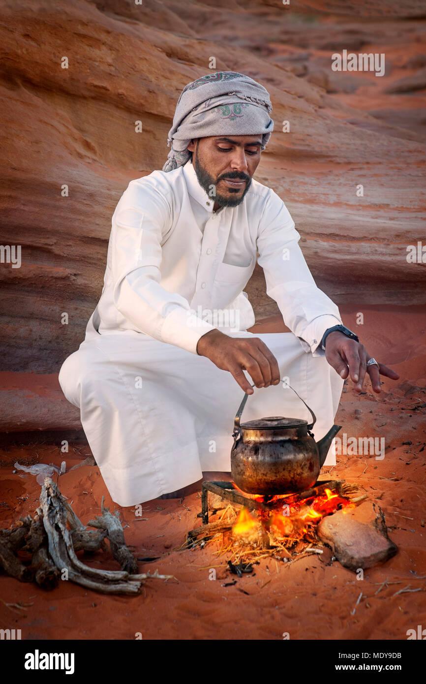 Young Bedouin man prepare traditional tea on the fire, Wadi Rum Desert, Jordan Stock Photo
