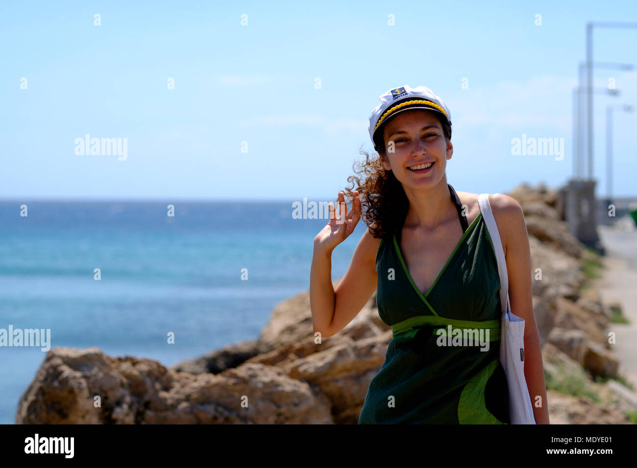 3d606963d Young woman in a green dress with a ship captain hat on a pier Stock ...