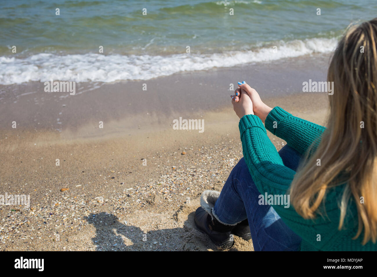 Young white woman relaxing outside on sunny sandy beach enjoying blue sea water. Horizontal color photography. - Stock Image