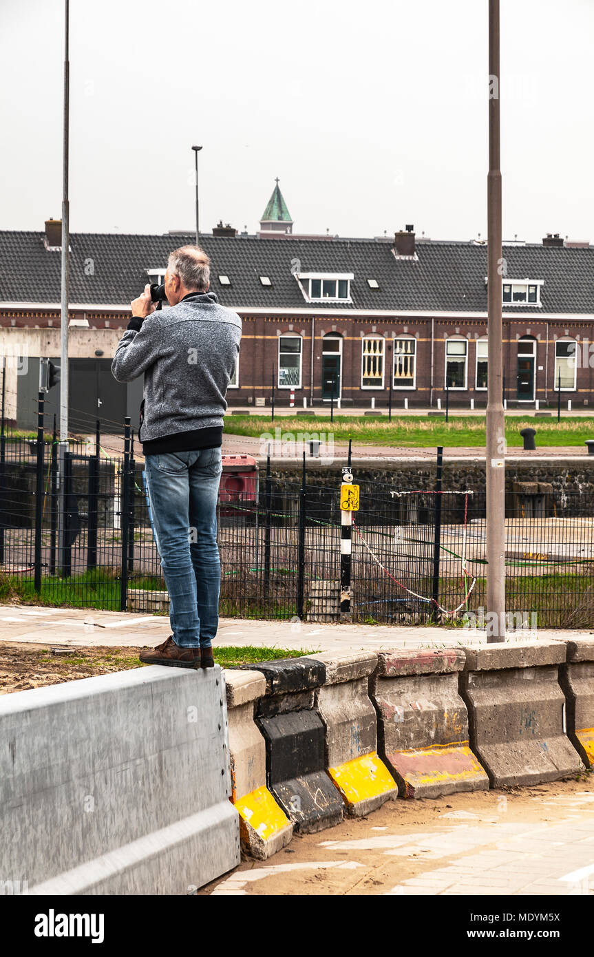 man stands on a concrete block to taking pictures - Stock Image