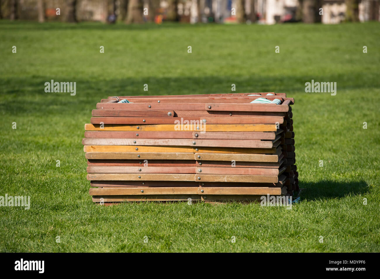 20 April 2018. Hot Spring weather in Green Park with stack of deckchairs, London, UK - Stock Image