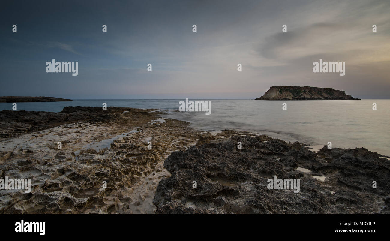 Rocky Seascape at dramatic sunset with the small  island of Geronisos at Paphos area Akamas peninsula in Cyprus - Stock Image