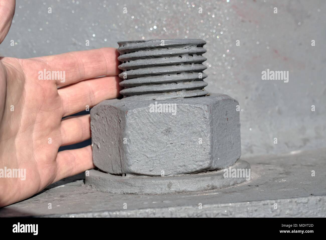 Technology,engineering,modernity and construction progress concept: large metal screw securing a high voltage pole,comparison with the hand of a man. - Stock Image
