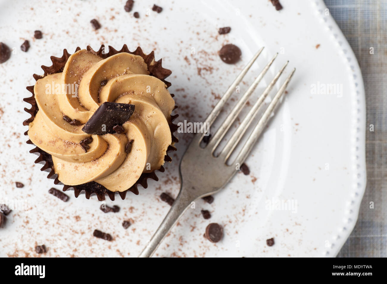 Salted Caramel cupcake on white plate with fork, dusted with cocoa powder and chocolate sprinkles, Overhead View - Stock Image