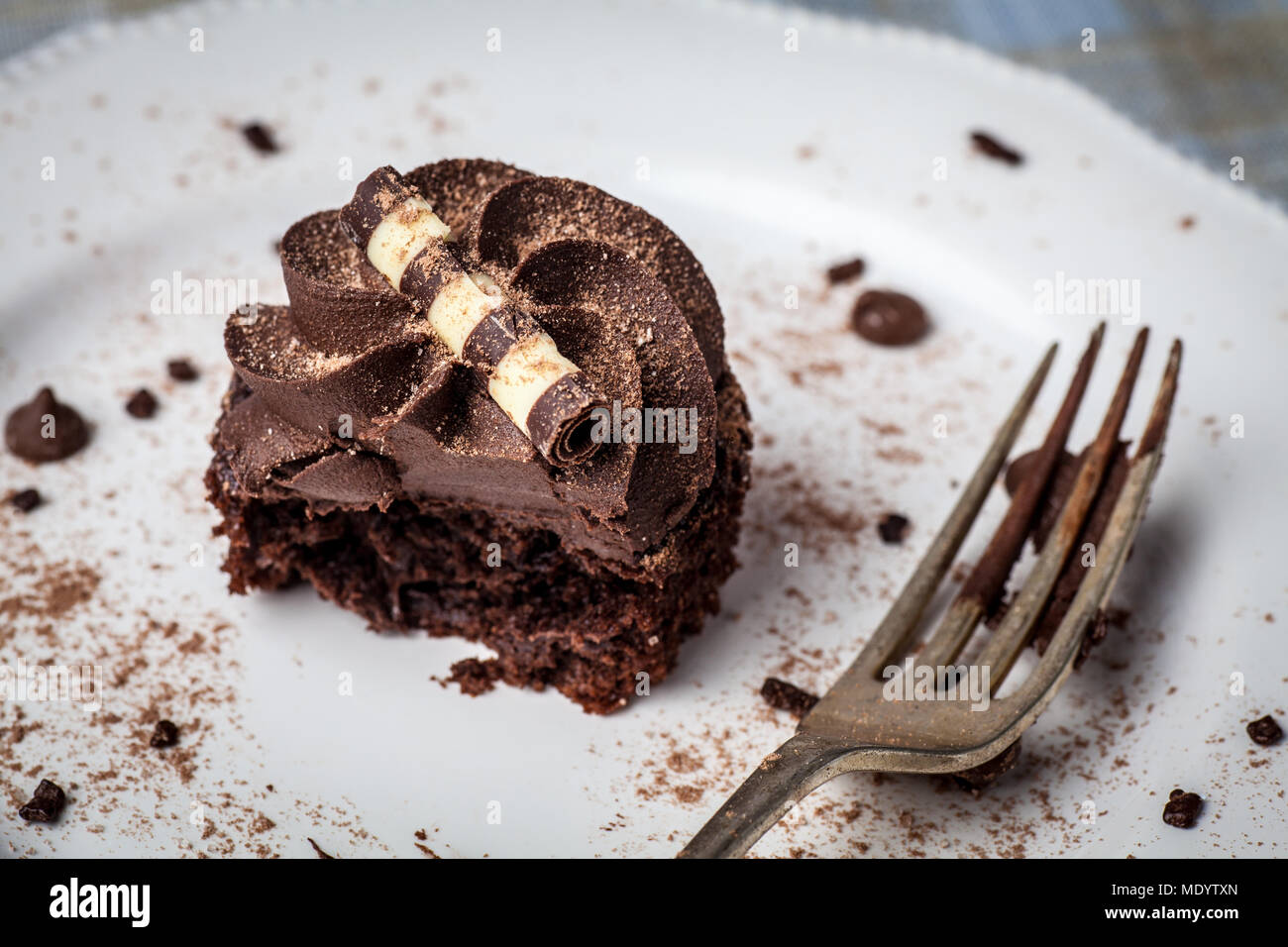 Chocolate cupcake on white plate with fork, dusted with cocoa powder and chocolate sprinkles, half eaten - Stock Image