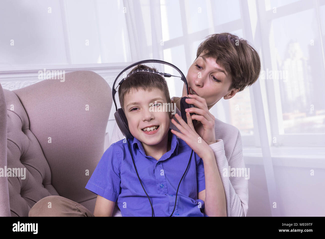 Mother screaming to her son while he listening music and doesn't listen - Stock Image