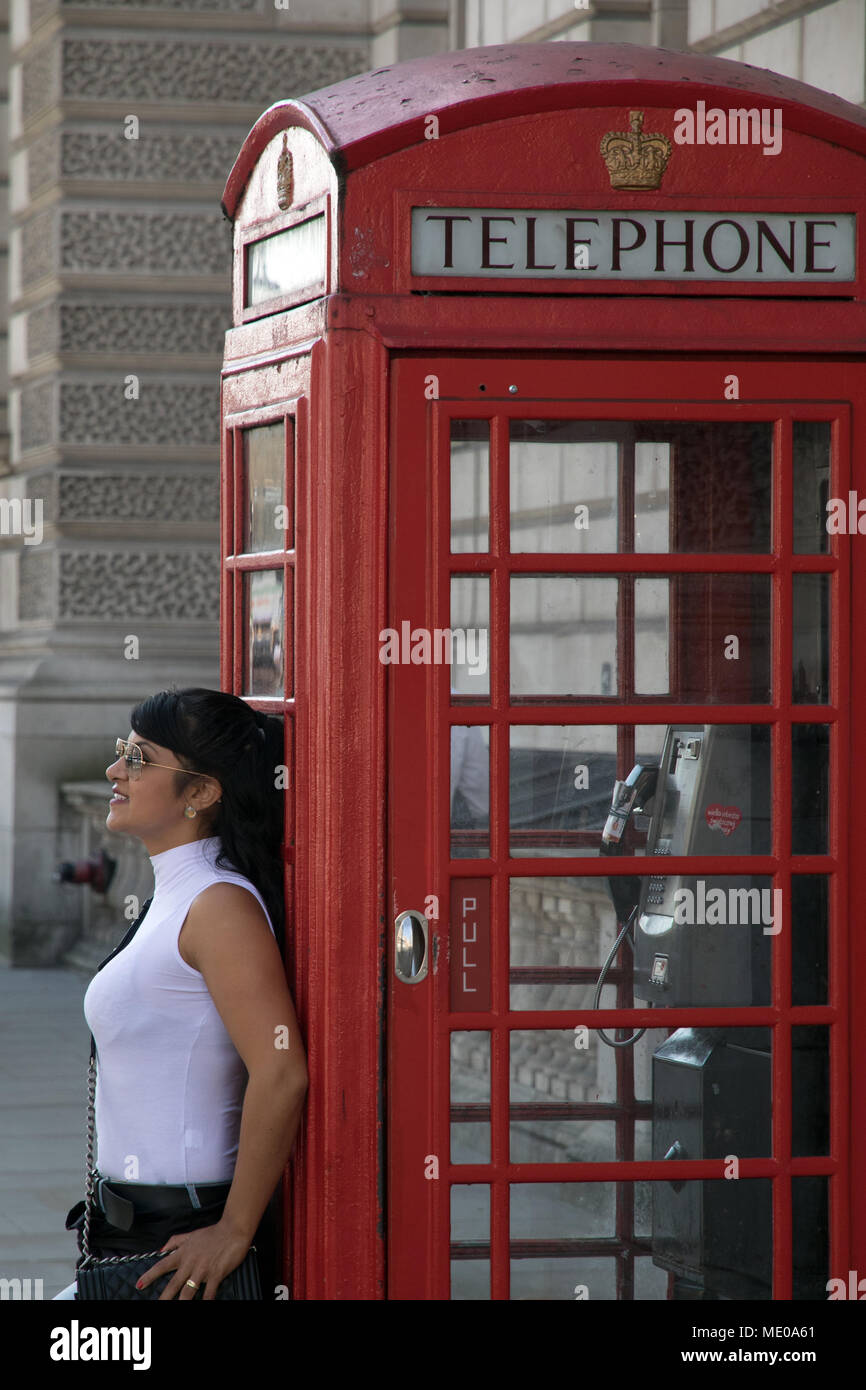 Young woman leaning against telephone kiosk in Whitehall London - Stock Image