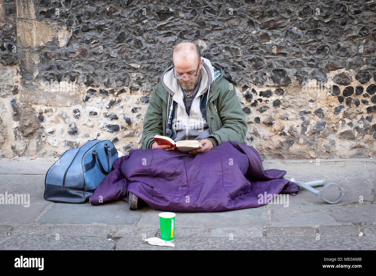 A homeless man sits on the pavement reading with cup ready to collect money donations in Canterbury Stock Photo