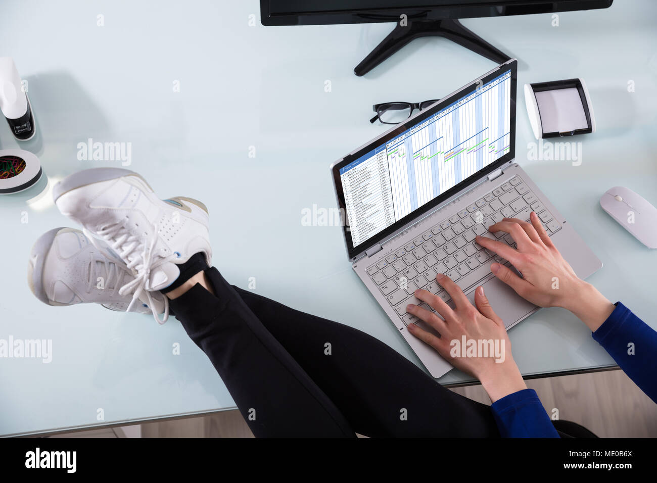Businessperson's Hand Working On Gantt Chart Using Laptop With Crossed Legs On Office Desk - Stock Image