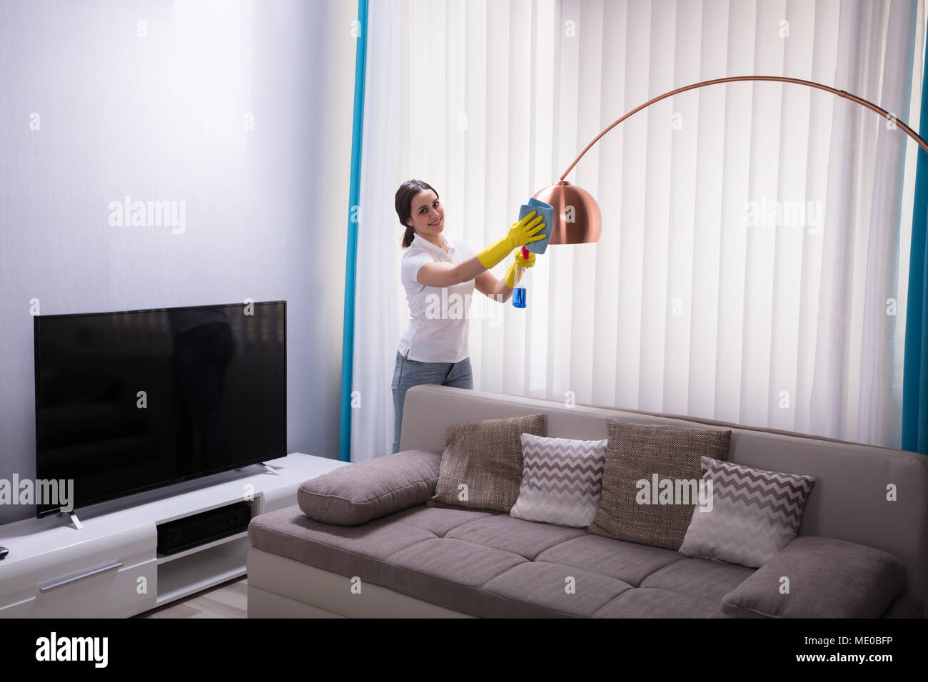 Young Female Janitor Cleaning Electric Light With Spray At Home - Stock Image