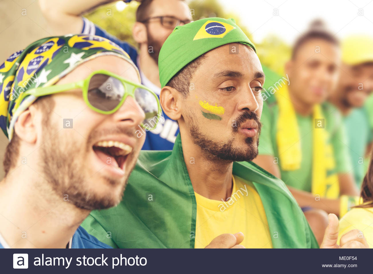 Group of fans cheer for brazilian team on stadium bleachers. Emotions portrait. - Stock Image