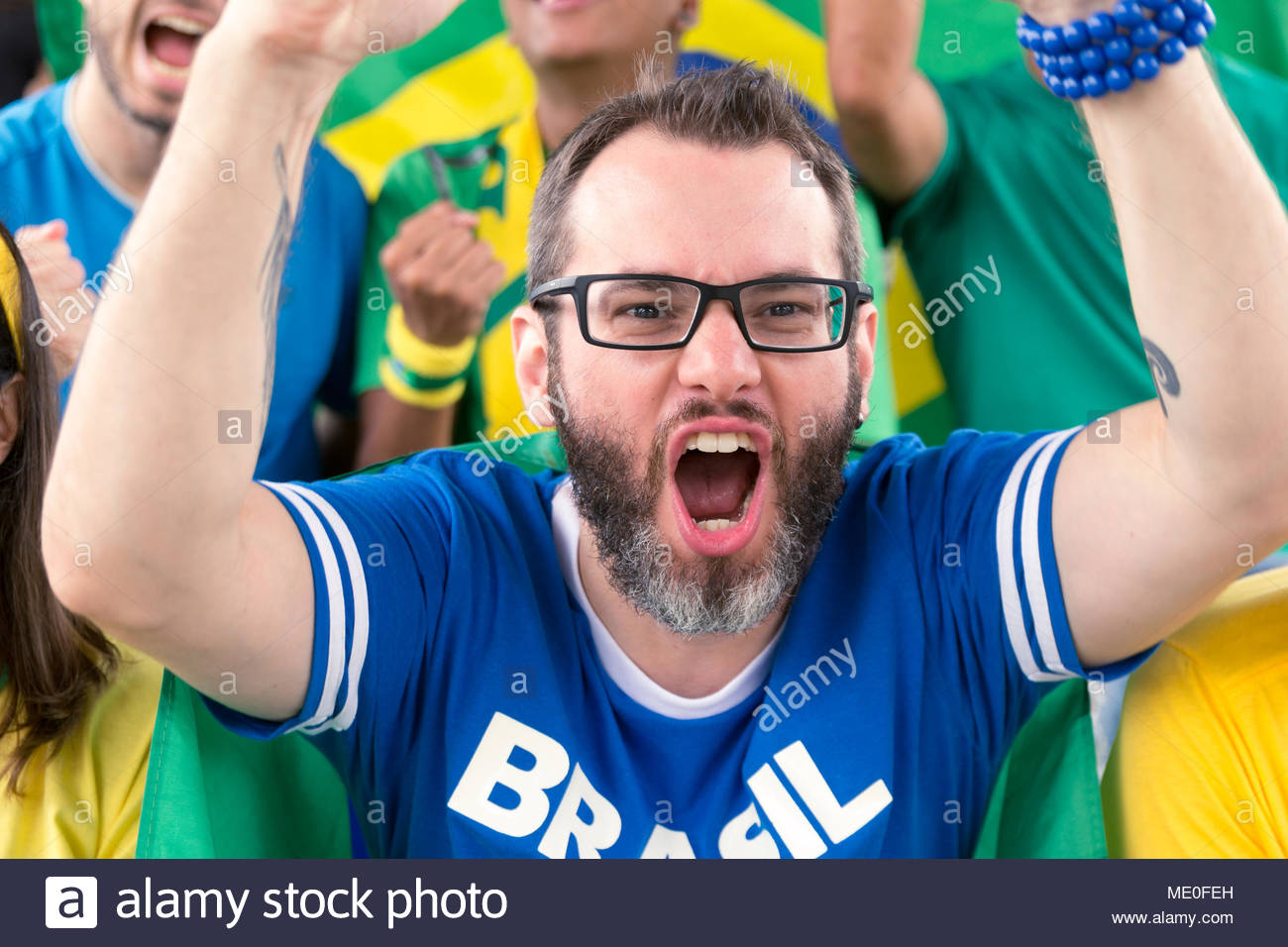 Group of fans cheer for brazilian team on stadium bleachers. Emotions portrait. Goal, victory, celebration.  Man wearing generic brandless blue t-shir - Stock Image