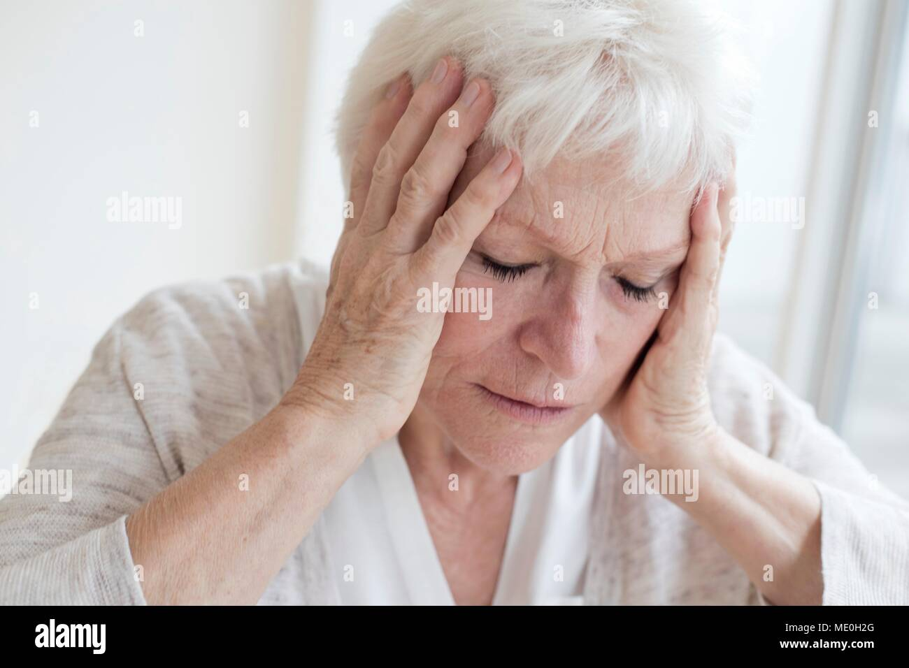 Senior woman with headache. - Stock Image