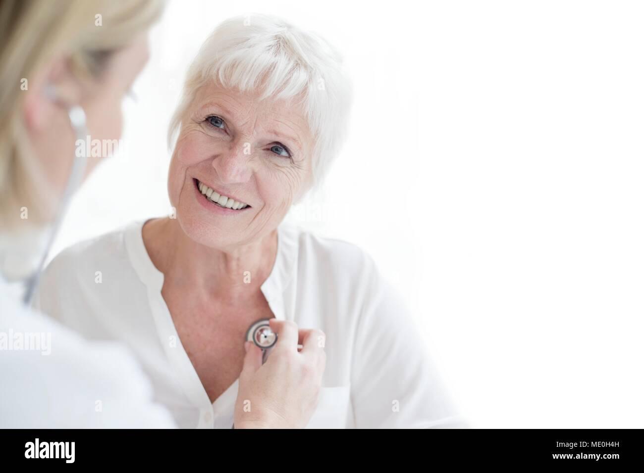 Female doctor examining senior woman. - Stock Image