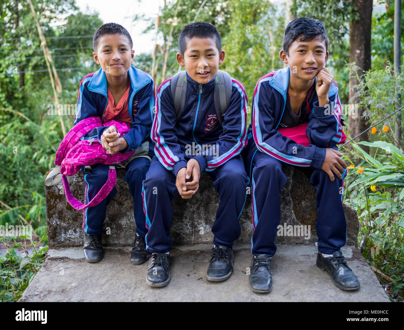 Portrait of three male students in uniform sitting on a concrete ledge, Glenburn Tea Estate; Darjeeling, West Bengal, India - Stock Image