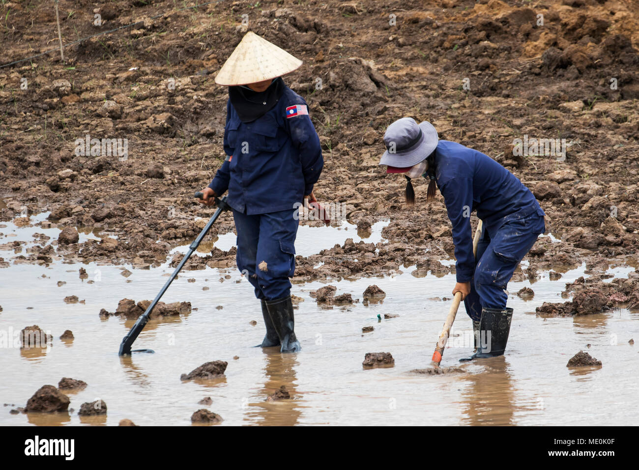 Women using a metal detector while clearing landmines in a