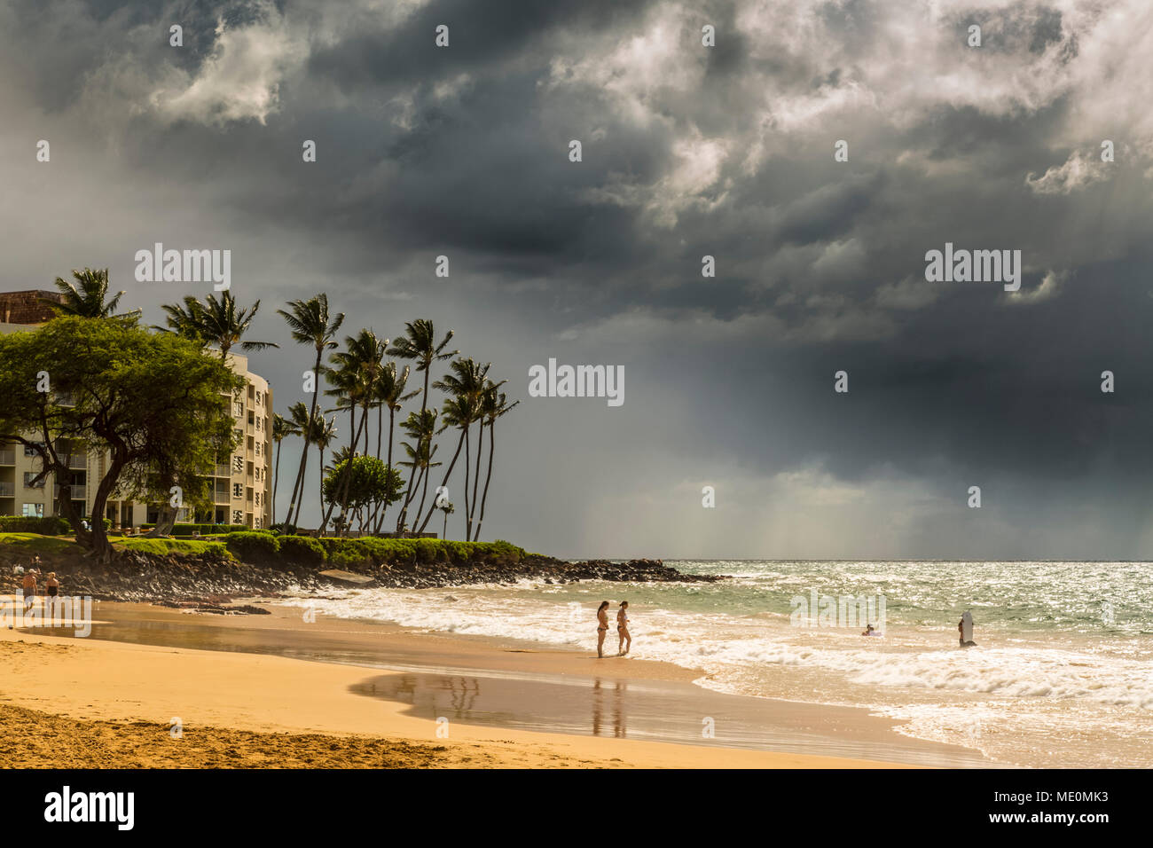 Tourists on a beach on the island of Maui with dark clouds and rainfall over the ocean in the distance - Stock Image