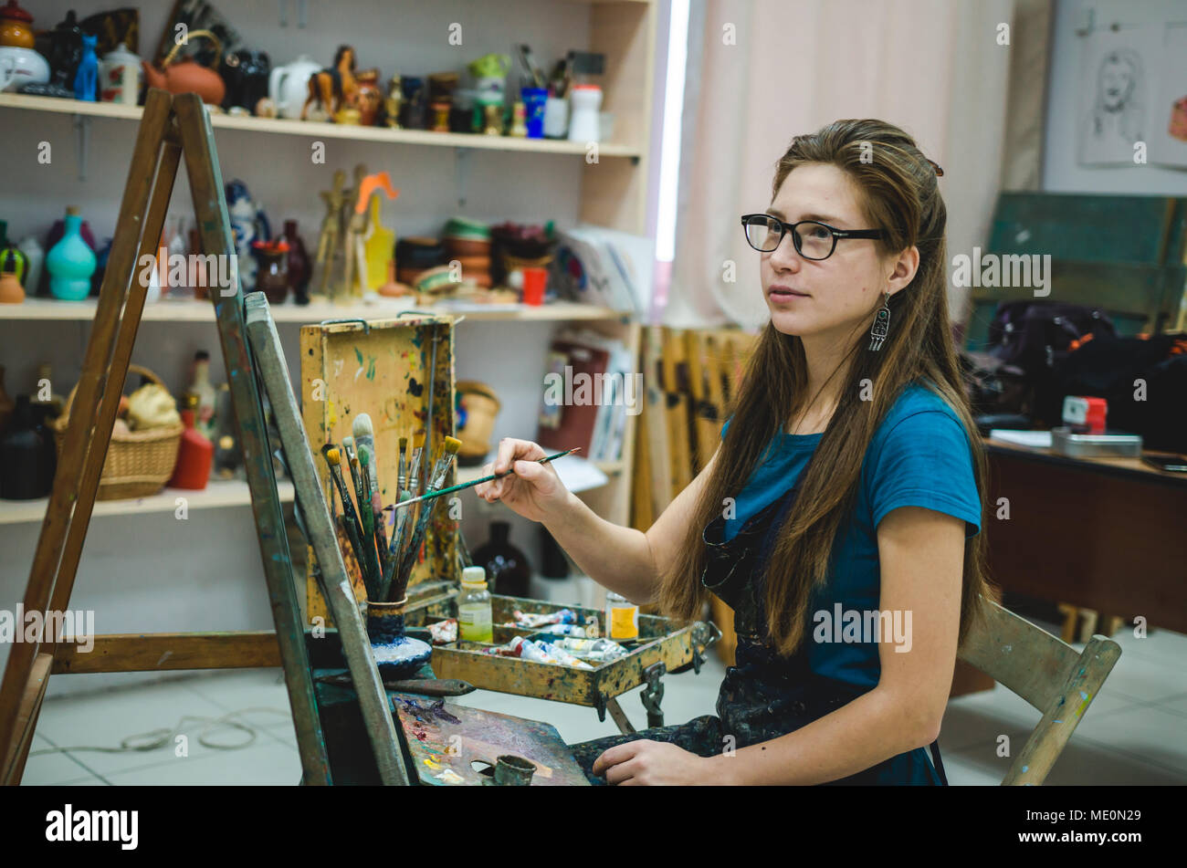 Pretty girl artist paints on canvas in art studio - Stock Image