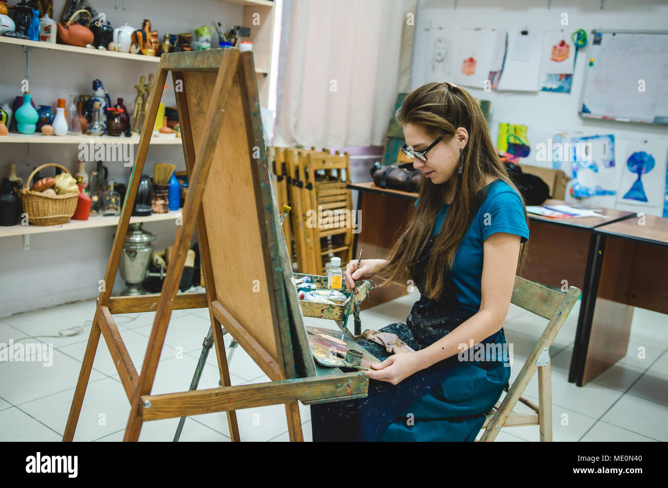 Female painter drawing in art studio using easel - Stock Image
