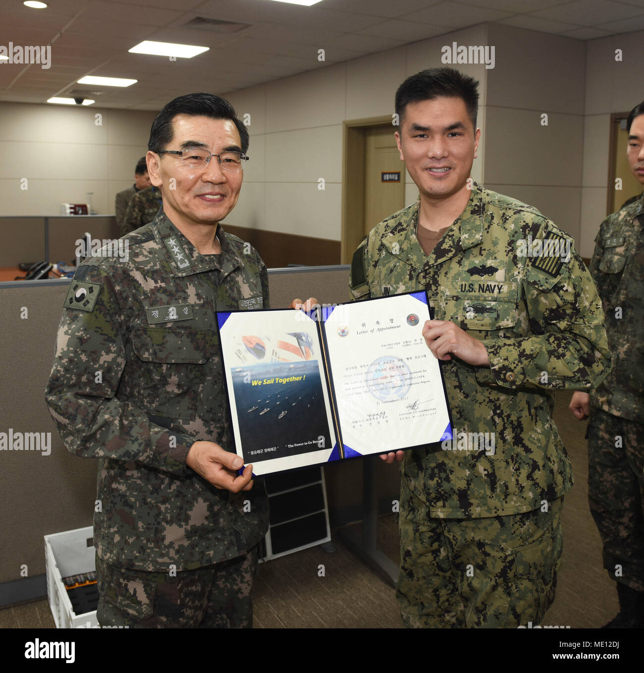 "171221-N-TB148-005 BUSAN, Republic of Korea (Dec. 21, 2017) Republic of Korea (ROK) Navy Vice Adm. Jung, Jin-Sup, commander, ROK Fleet, presents Lt.  Sean Jin with a letter of appointment for his selection to the ""Great Young Minds"" Junior Officers' Engagement and Cooperation Program. The ""Great Young Minds"" initiative brings together hand-selected, young officers from the ROK and U.S. navies and challenges them to develop innovative solutions to further enhance the ROK -U.S. alliance of the future. (U.S. Navy photo by Mass Communication Specialist Seaman William Carlisle) Stock Photo"