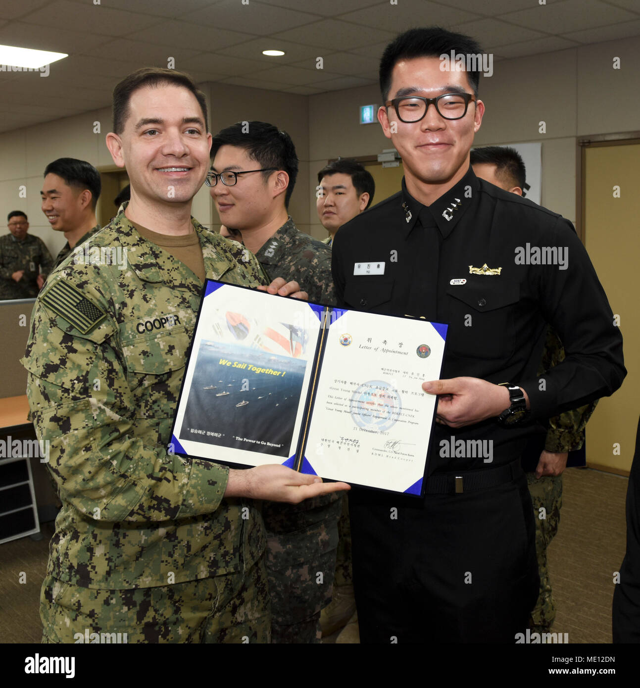 """171221-N-TB148-047 BUSAN, Republic of Korea (Dec. 21, 2017) Rear Adm. Brad Cooper, commander, U.S. Naval Forces Korea (CNFK), presents Lt. Yu, Jin Hong with a letter of appointment for his selection to the """"Great Young Minds"""" Junior Officers' Engagement and Cooperation Program. The """"Great Young Minds"""" initiative brings together hand-selected, young officers from the ROK and U.S. navies and challenges them to develop innovative solutions to further enhance the ROK -U.S. alliance of the future. (U.S. Navy photo by Mass Communication Specialist Seaman William Carlisle) Stock Photo"""