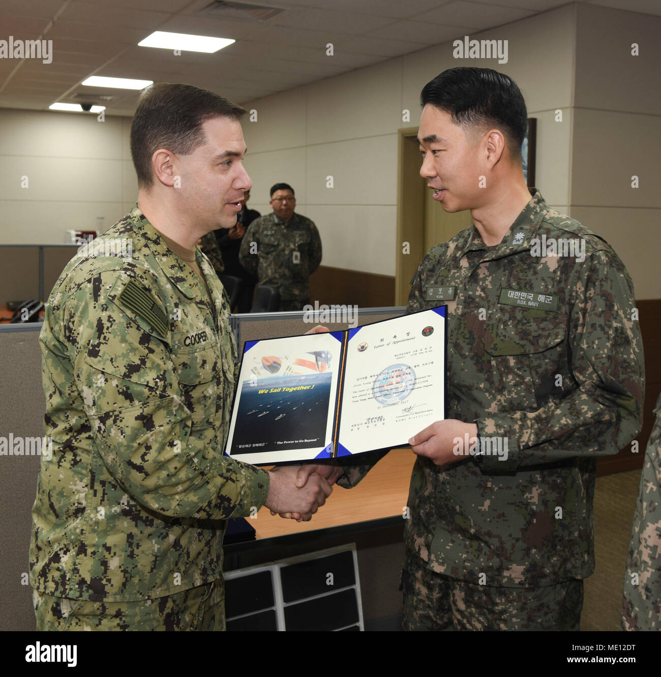 "171221-N-TB148-025 BUSAN, Republic of Korea (Dec. 21, 2017) Rear Adm. Brad Cooper, commander, U.S. Naval Forces Korea (CNFK), presents Lt. Cmdr. Kim, Bo Kyu with a letter of appointment for her selection to the ""Great Young Minds"" Junior Officers' Engagement and Cooperation Program. The ""Great Young Minds"" initiative brings together hand-selected, young officers from the ROK and U.S. navies and challenges them to develop innovative solutions to further enhance the ROK -U.S. alliance of the future. (U.S. Navy photo by Mass Communication Specialist Seaman William Carlisle) Stock Photo"