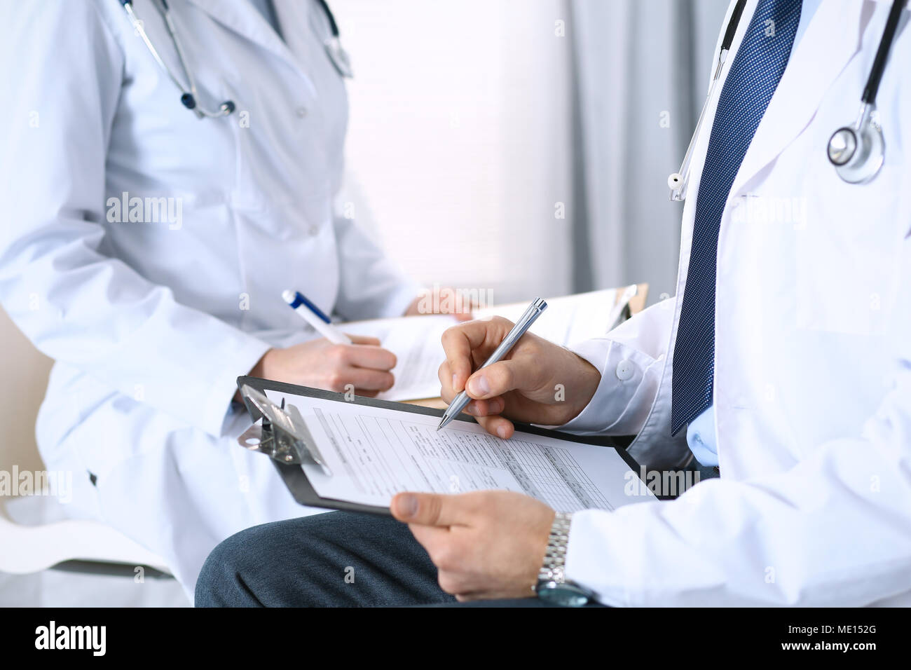Two unknown doctors filling up medical form on clipboard, just hands closeup. Physicians asking question to patient or discussing medication program. Healthcare, insurance and medicine concept - Stock Image