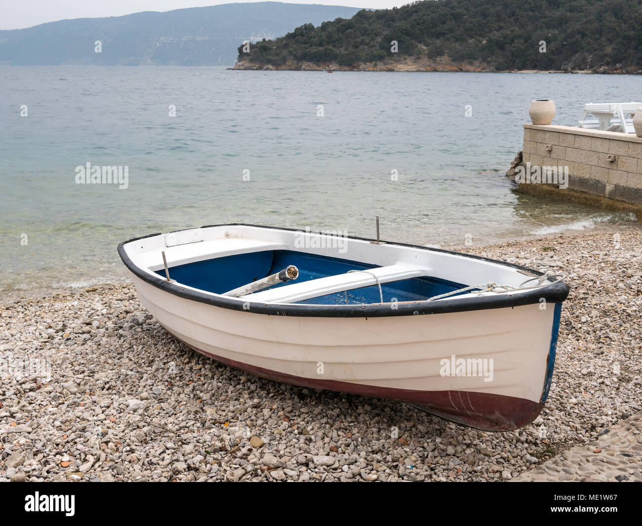 A small boat in the harbor of Valun (Island Cres, Croatia) on a cloudy day in spring Stock Photo