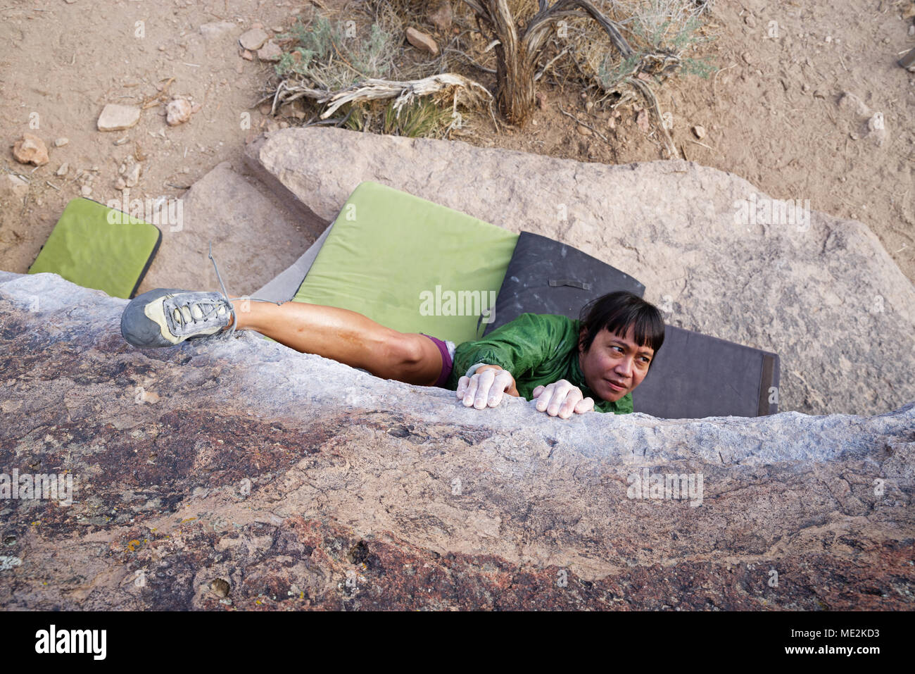 a woman bouldering on a traverse from above with a heel hook - Stock Image