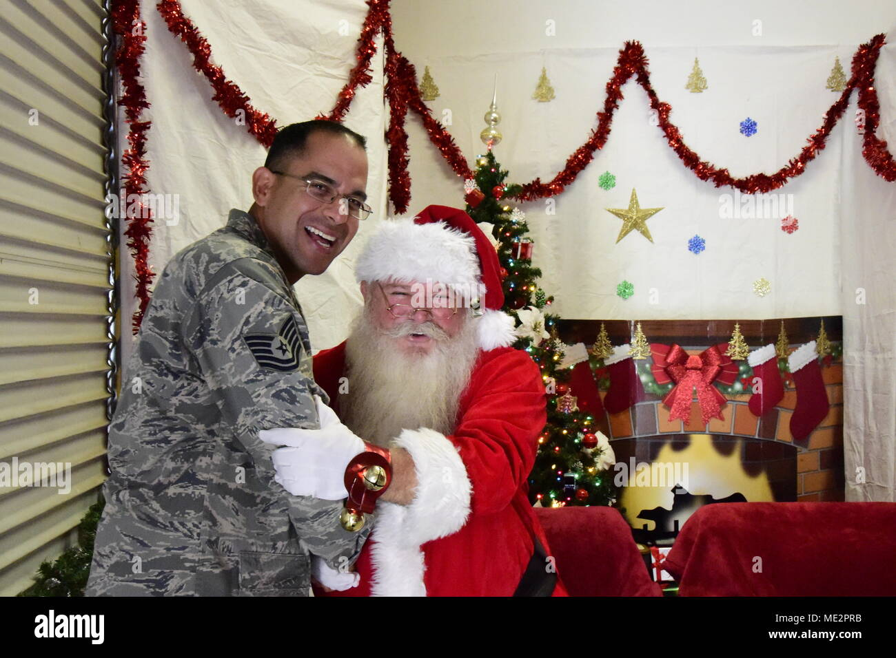 U.S. Air National Guard Tech. Sgt. Juan Marquez, a chaplain assistant with the 163d Attack Wing Chaplain Corps, left, embraces, retired Master Sgt. Christian Gavin, acting as Santa Claus during the annual Santa's Workshop at March Air Reserve Base, California, Dec. 2, 2017. Airmen with the wing's 210th Weather Flight organize the annual event to provide members and family with stocking stuffers and holiday cheer. - Stock Image