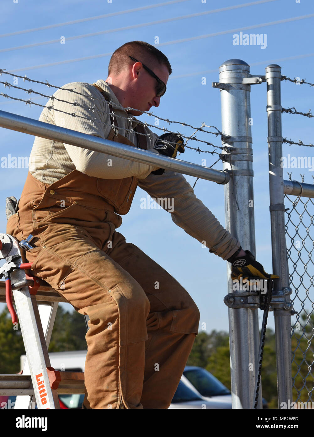 A U.S. Airman assigned to the 20th Civil Engineer Squadron constructs a fence for a new MQ-9 site at Shaw Air Force Base, S.C., Dec. 12, 2018. Airmen began construction following results from an environmental assessment, using available equipment to prevent additional costs to the government and to reduce time waiting for new equipment to be delivered. (U.S. Air Force photo by Airman 1st Class Kathryn R.C. Reaves) Stock Photo