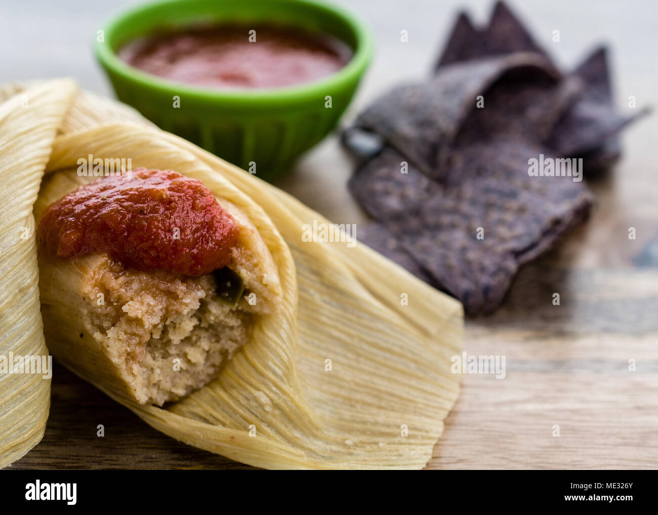 Partly unwrapped tamale served with blue corn tortillas and tomato sauce on wooden table side view - Mexican Food - Stock Image