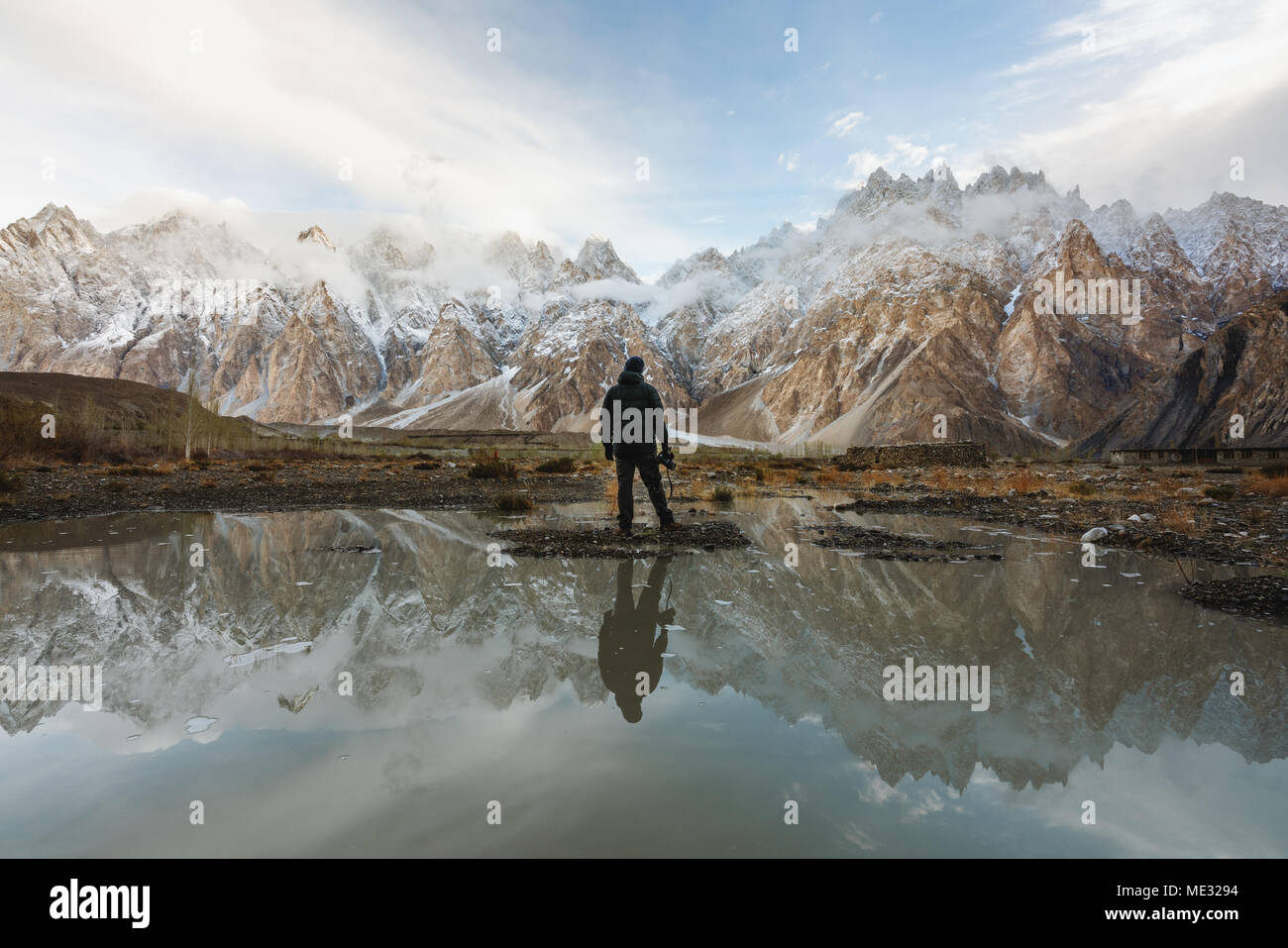 Photographer looking at Passu Cathedral mountain in Pakistan and reflection on the water - Stock Image