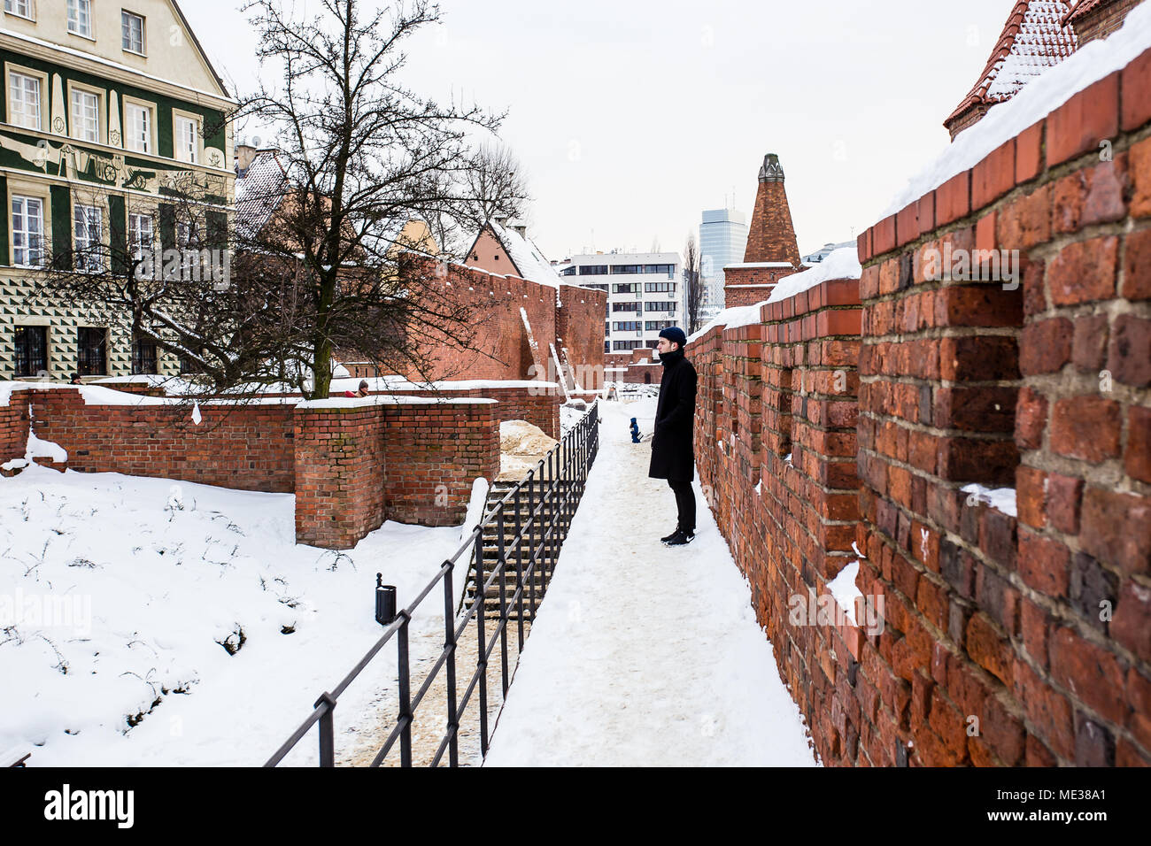 man standing against Warsaw barbican wall, looking out over the snow after snow storm. Warsaw, Poland - Stock Image