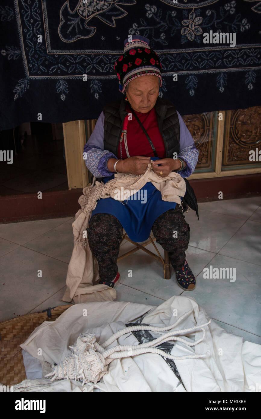 Dali, China - March 23, 2018: Bai woman hand dyeing fabrics with indico blue - Stock Image