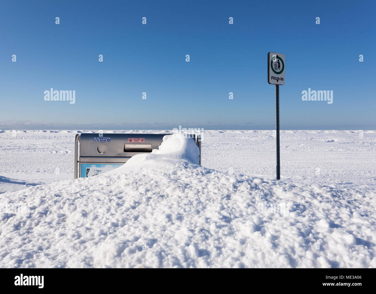 A garbage can almost completely buried in snow along the Georgian Bay Coastline at Wasaga Beach, Ontario, Canada. - Stock Image